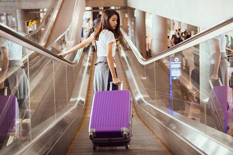 Mulher com mala de rodinha em shopping
